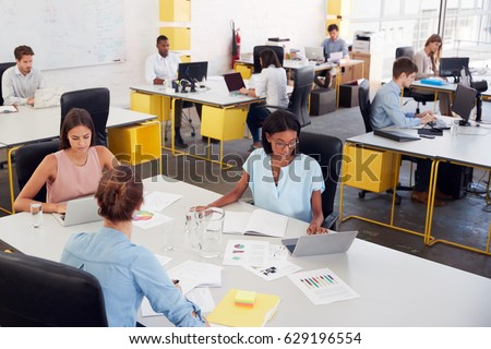 Three women share a desk in a busy office, elevated view