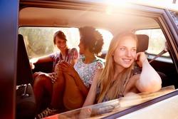 Three Women Sitting In Rear Seat Of Car On Road Trip