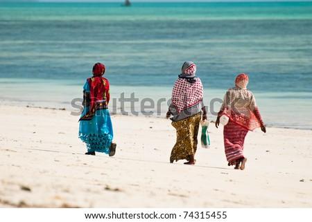 Three women walking on the beach in Jambiani, Zanzibar island, Tanzania