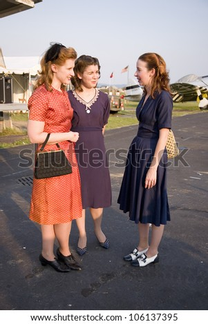 Three women wearing old fashioned 1940s dresses at Mid-Atlantic Air
