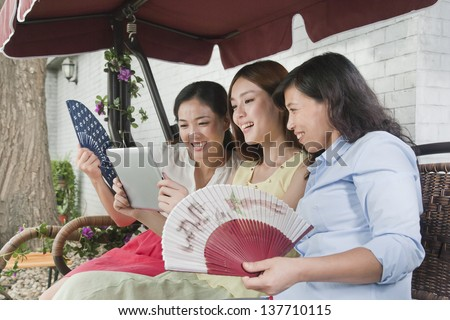 Three Women with Fans and Tablet Outdoors