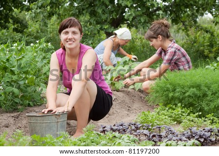 Three women working in her vegetable garden
