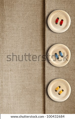 Three wooden button with colored threads on canvas background