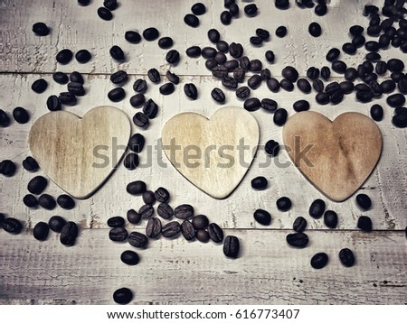 Three wooden cartoon heart placed nicely on the white background and coffee beans spread around them, in vintage style,for tell love someone or symbol who love coffee.   #616773407