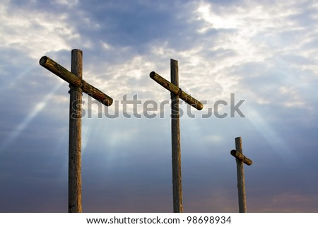 Three wooden crosses stand against a dramatic evening sky with radiant beams penetrating clouds. Great for Easter Sunday!