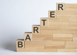 Three wooden cubes with letters BARTER on white table.