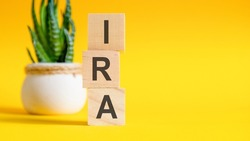 Three wooden cubes with letters - IRA on yellow table, space for text in right. Front view concepts, flower in the background. IRA - short for individual retirement account