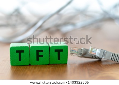Three wooden cubes with the lettering TFT beside grey lan cable on wooden table #1403322806