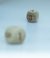 Three wooden dice in English numbers