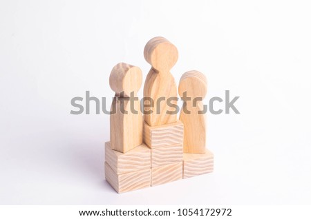 Three wooden figures of a man stand on the podium of the winners. The concept of victory, business competition and competition among employees. Olympiad and Paraolympic Games, Universiade #1054172972