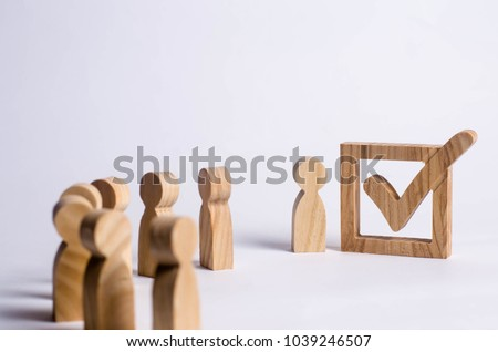 Three wooden human figures stand together next to a tick in the box. The concept of elections and social technologies. Volunteers, parties, candidates, constituency electorates. Human rights. - Shutterstock ID 1039246507