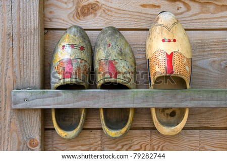 Three wooden shoes are hanging on the side of a barn on a farm