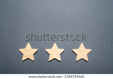 Three wooden stars on a gray background. The concept of quality and prestige. High quality and reliability, universal acceptance. Rating and status of the restaurant or hote. best Choice #1304194666