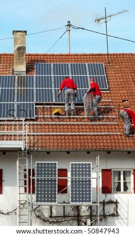 three worker installing solar panels on roof