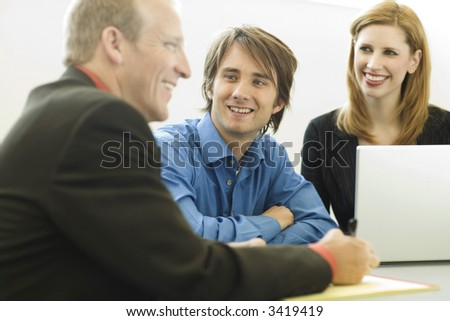 Three workers sit and talk at a desk