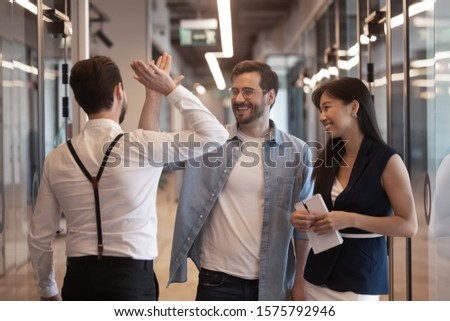 Three workers standing in office hallway talking, millennial guys caucasian businessmen colleagues meet greeting glad to see each other giving high five gesture of respect friendly relations concept