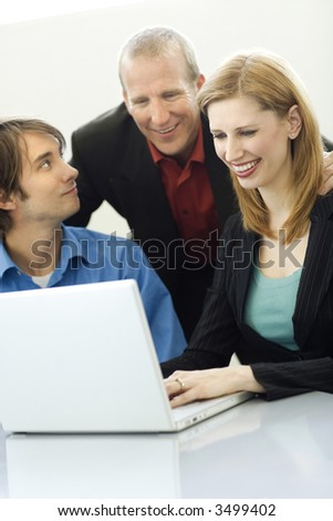 Three workers talk while using a laptop