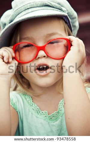 Three-year-girl in glasses and a cap, fashion - stock photo