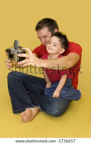 Three year old boy taking family photo with digital camera.