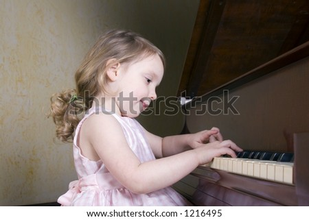 Three year old girl playing the piano - stock photo