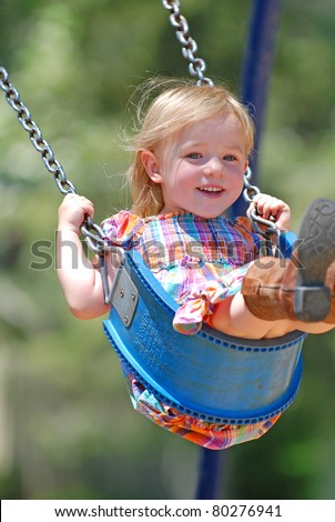 Three year old girl swinging high in a swing smiling.