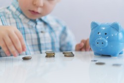 three years old boy puts money in a piggy bank, piggybank concept. mantesori space in the house