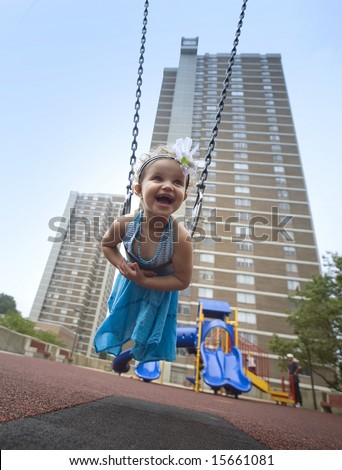 three years -old girl on a swing in the playground