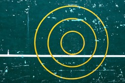 Three yellow concentric circle on the spotted green cement wall with another white level line is tangent with the smallest circle. The concept for target, practice, concentration.