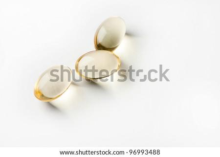 Three yellow pills on white background