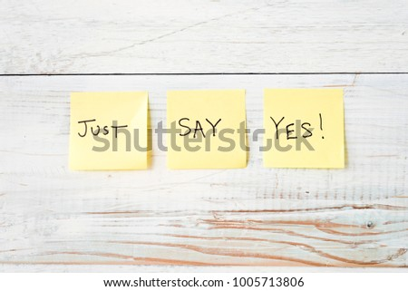 three yellow Post It notes with message Just Say Yes! against weathered white wood background #1005713806