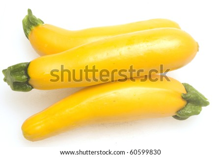 three yellow zucchini squash  on white cutting board