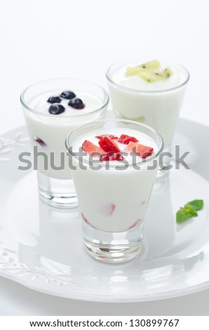 three yogurt with fruit in a glass beaker on a plate vertical closeup