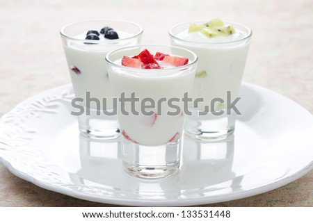 three yogurt with various fruits on a plate
