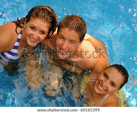 Three young adults enjoy a relaxing day in the pool on a hot summer day.