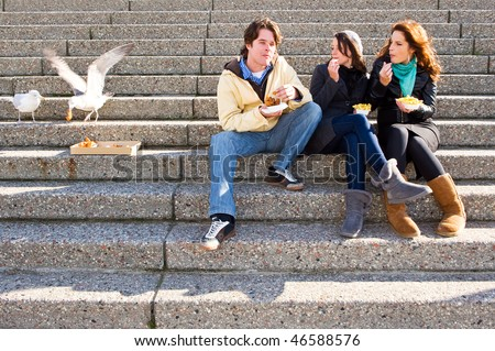 Three young adults sitting on concrete stairs, eating fish and chips, whilst two seagulls steal a bit of cod cheeks,