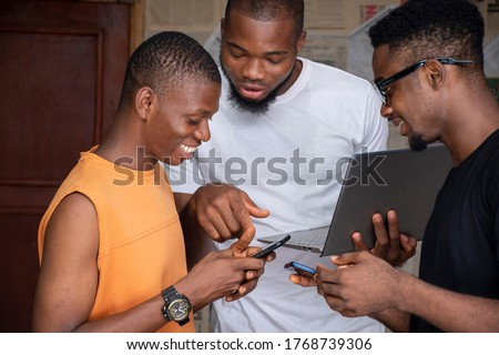 three young african people using their mobile phones and laptops simultaneously sharing content