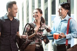 Three young and cheerful employees wearing trendy casual clothes while talking together in the morning in a modern workplace