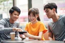 three young asian adults sitting in outdoor coffee shop using cellphone together