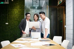 three young asian entrepreneurs meeting in office discussing business using laptop computer