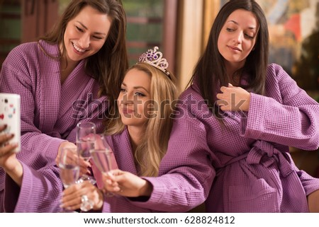 three young beautiful happy girls doing Selfy on bachelorette party at a luxury spa with champagne