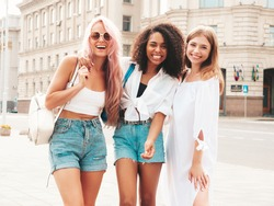 Three young beautiful smiling hipster female in trendy summer clothes.Sexy carefree multiracial women posing on the street background.Positive models having fun in sunglasses. Cheerful and happy