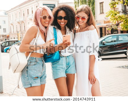 Three young beautiful smiling hipster female in trendy summer clothes.Sexy carefree multiracial women posing in the street.Positive models in sunglasses. Looking at smartphone screen.Using phone apps