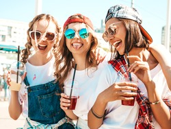 Three young beautiful smiling hipster female in trendy summer clothes.Sexy carefree women posing outdoors.Positive models holding and drinking fresh cocktail smoothie drink in plastic cup with straw