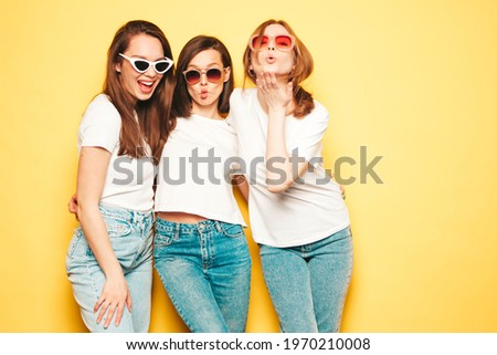 Three young beautiful smiling hipster female in trendy summer white t-shirt and jeans clothes.Sexy carefree women posing near yellow wall in studio.Positive models going crazy. Making funny faces