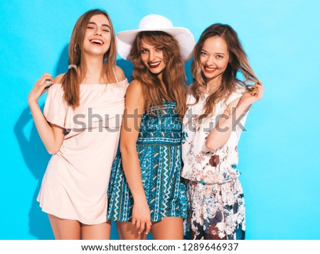 Three young beautiful smiling hipster girls in trendy summer casual dresses. Sexy carefree women posing near blue wall. Positive models going crazy #1289646937
