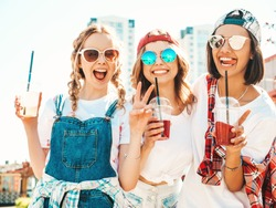Three young beautiful smiling hipster girls in trendy summer clothes.Sexy carefree women posing outdoors.Positive models holding and drinking fresh cocktail smoothie drink in plastic cup with straw
