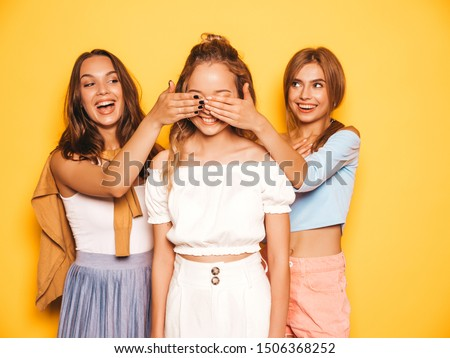 Three young beautiful smiling hipster girls in trendy summer clothes.Sexy carefree women posing near yellow wall in studio.Models surprising their friend.They cover her eyes and hugging from behind