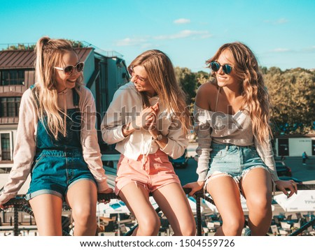 Three young beautiful smiling hipster girls in trendy summer clothes.Sexy women sitting on handrail in the street.Positive models having fun in sunglasses.They communicating and discussing something