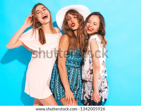 Three young beautiful smiling hipster girls in trendy summer colorful dresses. Sexy carefree women in isolated on blue. Positive models going crazy and making funny faces #1342005926