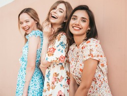 Three young beautiful smiling hipster girls in trendy summer sundress.Sexy carefree women posing on the street near wall. Positive models having fun and hugging.